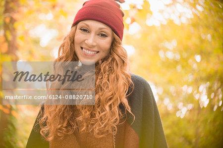 Portrait smiling woman in stocking cap under autumn trees