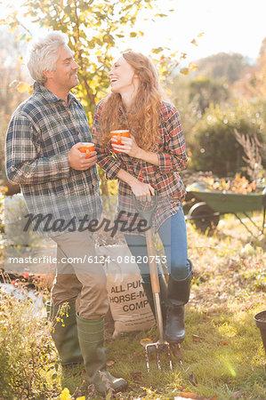 Couple laughing enjoying coffee break gardening sunny autumn garden