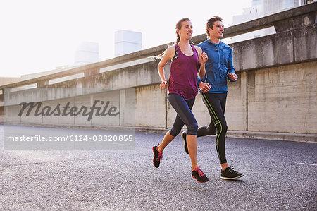Runner couple running on urban street