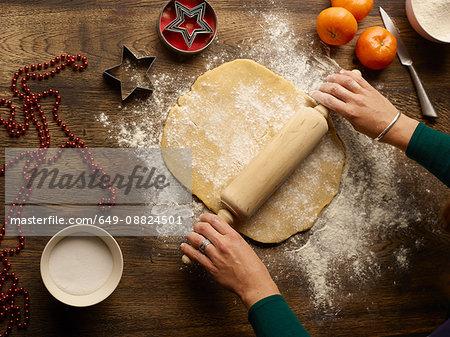 Overhead view of teenage girl's hands rolling christmas star biscuit dough