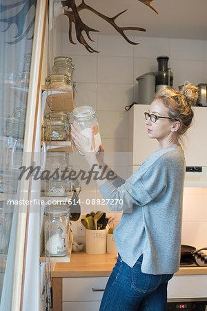 Woman reading label on kilner jar in kitchen