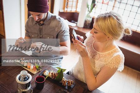 Couple taking photo of sushi