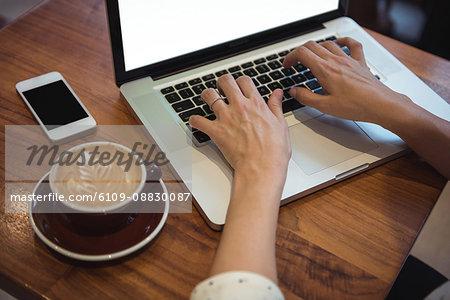 Businesswoman using laptop at café̩ table