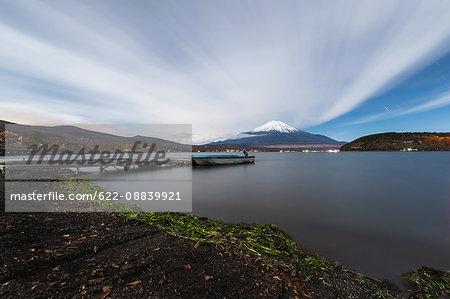 Night view of cloudy sky and Mount Fuji at night from Lake Yamanaka, Yamanashi Prefecture, Japan