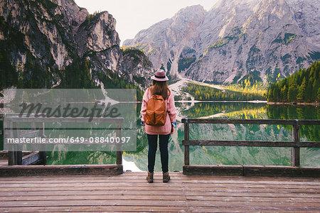 Woman enjoying view on pier, Lago di Braies, Dolomite Alps, Val di Braies, South Tyrol, Italy