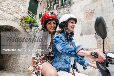 Female tourists riding moped through village, Split, Dalmatia, Croatia