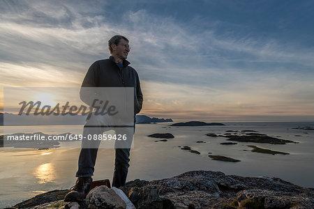 Man climbing a summit on Kvaloya Island in autumn, Arctic Norway
