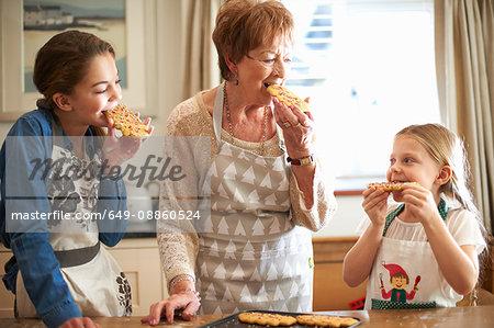 Senior woman and granddaughters eating freshly baked Christmas tree cookies