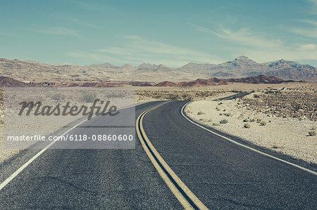 Curving road through desert, near Death Valley National Park, USA.