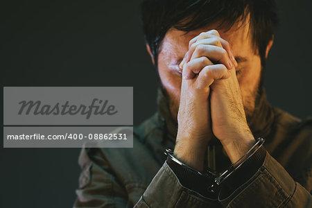 Handcuffed male prisoner in military uniform is praying in dark jail interior