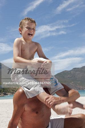 Older man with grandson on beach