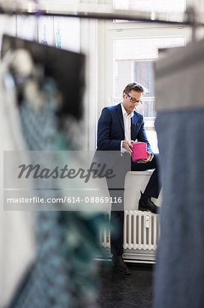 Businessman examining thread in office
