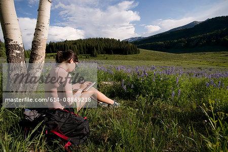 Hiker writing in grassy meadow