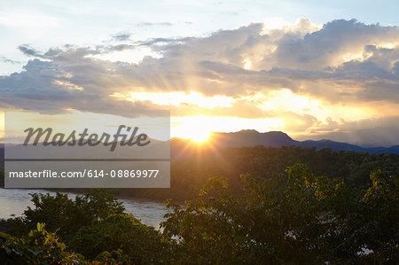 Sun rising over mountain range