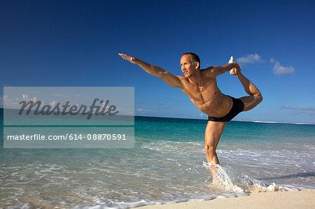 Man practicing yoga on tropical beach