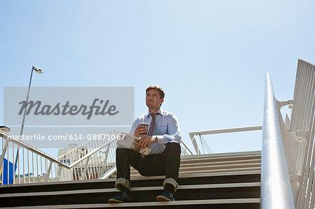 Businessman sitting on city steps