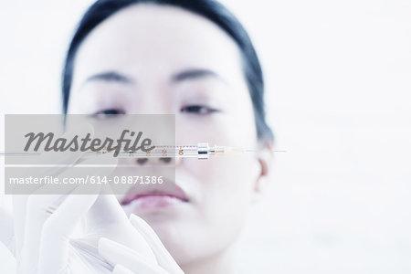 Woman examining syringe
