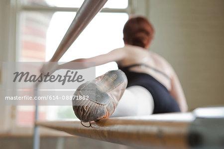 Ballet dancer warming up, foot on bar