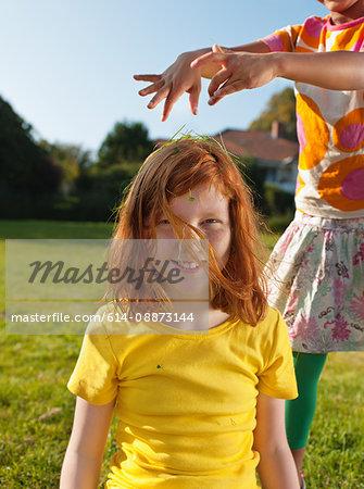 Girl putting grass on friends head, portrait