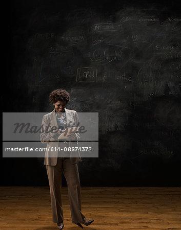 Woman by blackboard using digital tablet