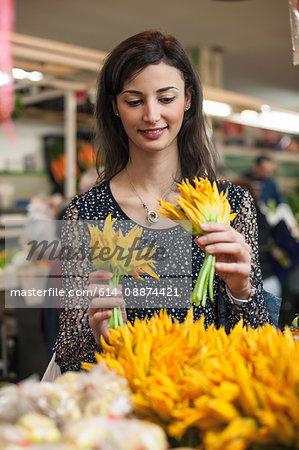 Woman choosing yellow flowers in market