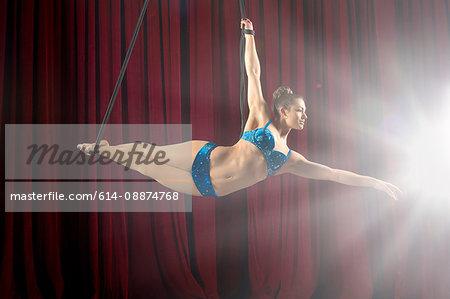 Studio shot of female aerialist poised on ropes