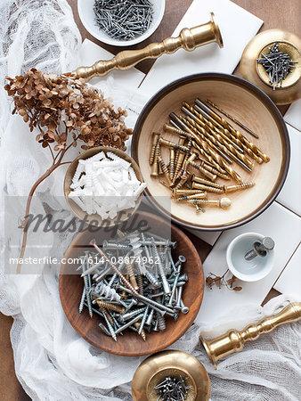 Still life of screws, nails and brass candlesticks