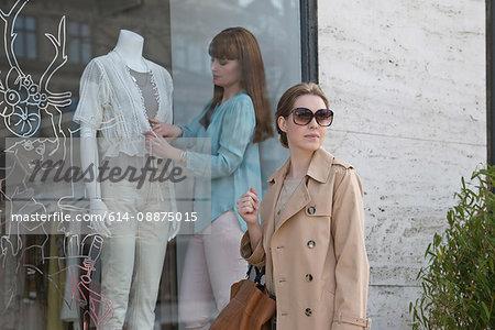 Woman dressing mannequin in shop window