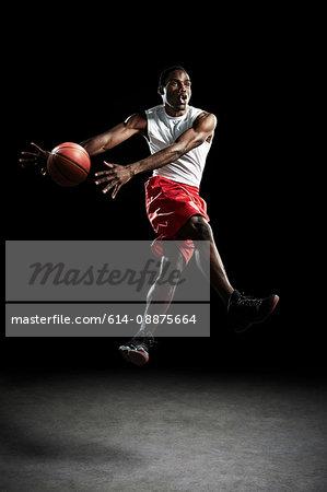 Young male basketball player throwing ball