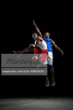 Male basketball players jumping and shooting ball