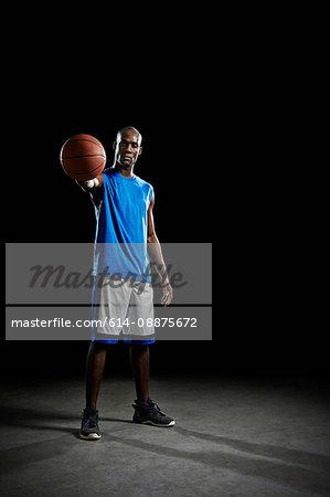 Studio portrait of basketball player holding ball