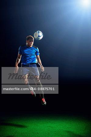 Male soccer player heading ball