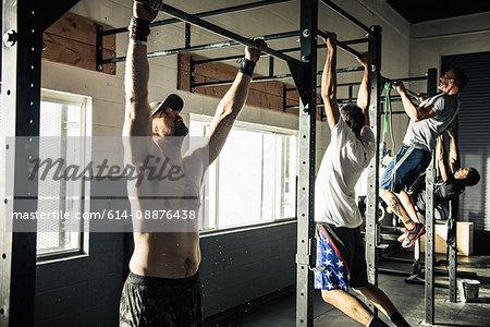 Men training on exercise bars in gymnasium