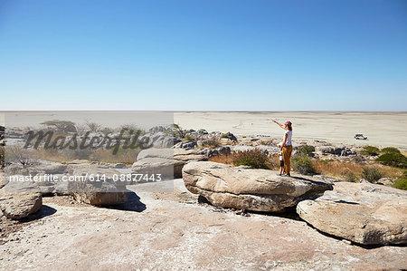 Mother and son on rock, Kubu Island, Makgadikgadi Pan, Botswana, Africa