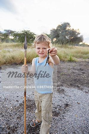 Portrait of young boy holding spear and scorpion, Otavi, Etosha, Namibia