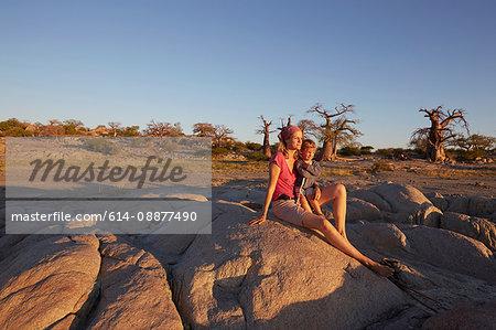 Mother and son sitting on rock, looking at view, Gweta, makgadikgadi, Botswana