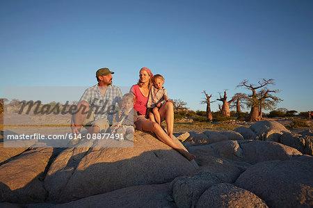 Family sitting on sitting on rock, looking at view, Gweta, makgadikgadi, Botswana
