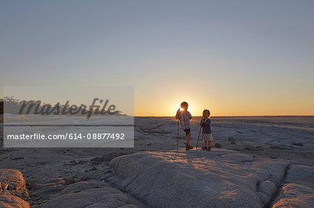 Two boys standing on rock, holding spear, sunset, Gweta, makgadikgadi, Botswana