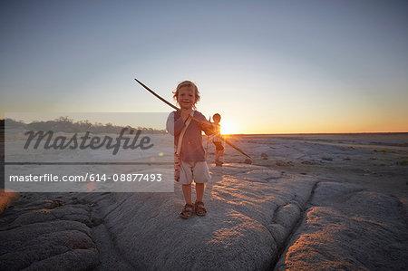Portrait of young boy standing on rock, holding spear, sunset, Gweta, makgadikgadi, Botswana
