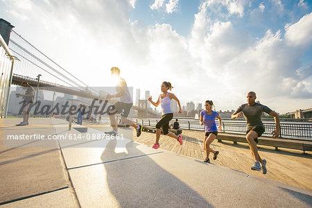 Four running friends running up riverside stairs, New York, USA