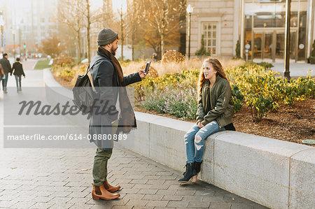 Young couple taking photograph in city, Boston, Massachusetts, USA