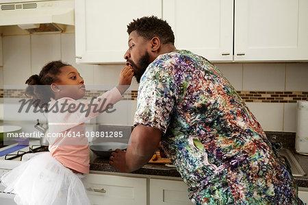 Girl feeding father in kitchen