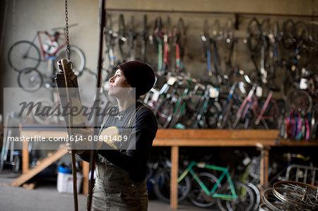 Female metalsmith attaching metal to chain hoist in workshop