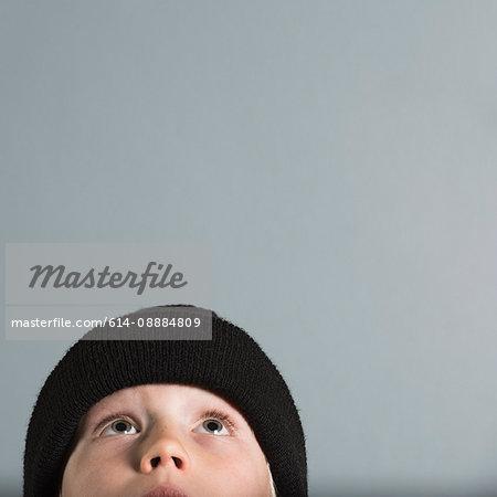 Portrait of boy wearing wool hat looking up
