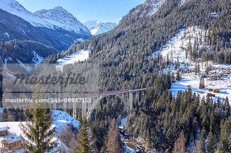 Red train of Rhaetian Railway on Langwieser Viaduct surrounded by snowy woods, Canton of Graubunden, Switzerland, Europe
