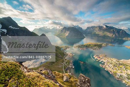Clouds reflected in blue lake and sea framed by rocky peaks, Reinebringen, Moskenesoya, Lofoten Islands, Norway, Scandinavia, Europe