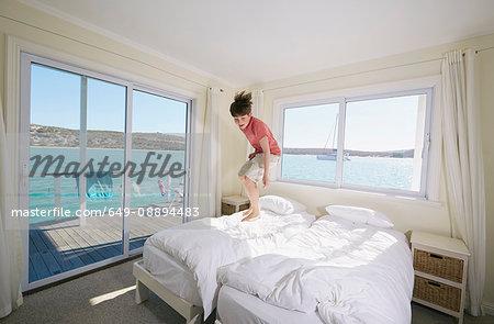 Boy jumping on bed in houseboat, Kraalbaai, South Africa