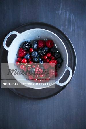 Summer berries in a light blue colander