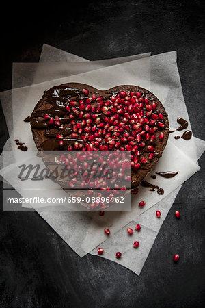 Heart-shaped chocolate cake with chocolate glaze and pomegranate seeds