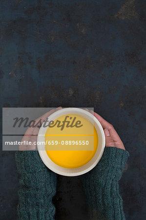 Hands holding a cup of hot sea buckthorn tea
